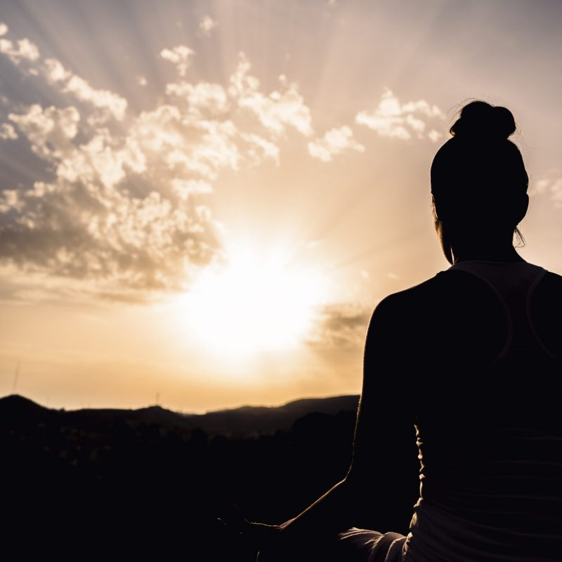 woman-during-meditation-with-the-sunset